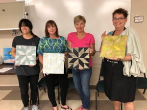 attendees holding their mini barn quilt paintings